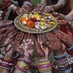 Indian Hindu married women perform rituals on Karva Chauth festival in Ahmadabad, India. Married women decorate their hands with henna on Karva Chauth festival and observe a fast to pray for the longevity and well-being of their husbands. (AP Photo/Ajit Solanki)<span class=