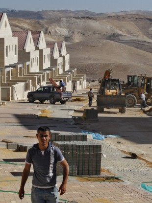 A Palestinian worker walks at a construction site in the West Bank Jewish settlement of Maaleh Adumim, near Jerusalem in 2009.
