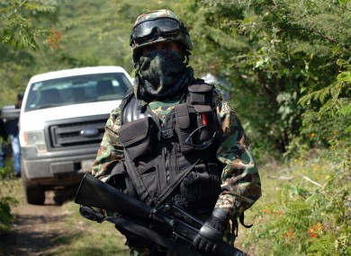 A Mexican navy marine guards the road that leads to the grave site.