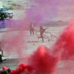Afghanistan's National Army soldiers make a mock attack on an enemy's stronghold using coloured flares for cover during a military exercise at Kabul Military Training Centre, in Kabul. (AP Photo/Massoud Hossaini)<span class=