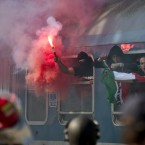 Chanting Hungarian soccer fans hold flares while arriving on a train at a railway station in Bucharest, Romania. Romanian authorities took exceptional security measures to prevent violence between soccer fans ahead of a Euro 2016 Group F qualifier soccer match between Romania and Hungary.(AP Photo/Vadim Ghirda)<span class=