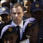 Oscar Pistorius is escorted by police officers as he leaves the high court in Pretoria, South Africa. Following the testimony hearing, which is expected to end this week, Judge Thokozile Masipa will rule on what punishment Pistorius must serve after convicting him of culpable homicide for shooting his girlfriend Reeva Steenkamp through a toilet door in his home.<span class=