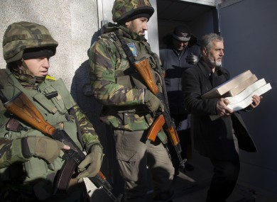 Ukrainian army soldiers guard a district election commission as an election official carries ballots to a polling station.