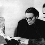 Margarete Himmler, wife of the German S.S. Chief who died by suicide, centre, as she reads over some papers with her daughter Gudrun, right, as they are watched by Louise Cuyon-Witzschel, who was secretary at the S.S. Headquarters in Italy, at Nuremberg, Germany, where they are waiting to testify in the trial.<span class=