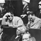 Rudolf Hess, right, holds his head during the war criminal trials at Nuremberg. <span class=