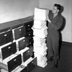 The translation division, holding a pile of transcripts representing one-fifth of those taken during the evidence given in court during the trial.<span class=