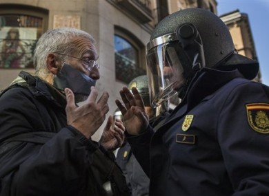 A policeman communicates with a demonstrator by a cordoned off street, during a protest against Spanish Citizens Security Law in Madrid.