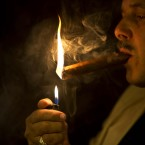 A man lights a cigar in a cigar club shop in Havana, Cuba. The coveted Cuban cigar is set to make its first legal appearance in the U.S. in years, with relaxed guidelines allowing American travelers to return with a few of the once-forbidden items in their suitcases. (AP Photo/Ramon Espinosa)<span class=