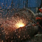 An Indian worker works at an iron and steel scrap workshop at an industrial area on Reay Road in Mumbai, India. (AP Photo/Rafiq Maqbool)<span class=