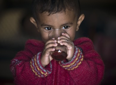 A Syrian Kurdish refugee child from the Kobani area, drinks tea at a camp in Suruc