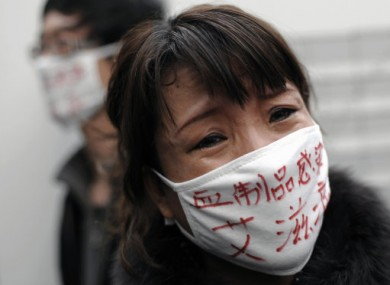 File photo: A woman whose son was infected with HIV, wearing a face mask baring the words