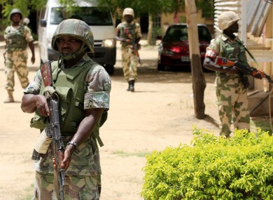 Nigerian soldiers stand guard at the offices of the state-run Nigerian Television Authority in Maiduguri.