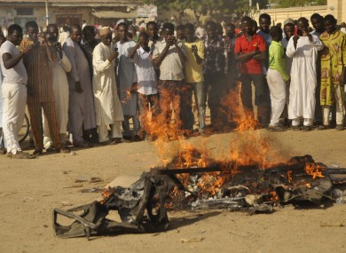 People gather at the site of a bomb explosion in Kano.