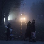 People cross tram lines in a fog in Mariupol, Ukraine. European Union leaders are threatening fresh sanctions against Russia because of what it sees as