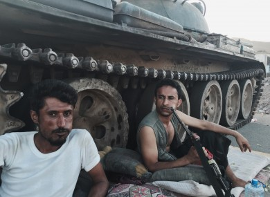 Members of a militia group loyal to Yemen's President Abed Rabbo Mansour Hadi, known as the Popular Committees, chew qat as they sit next to their tank, guarding a major intersection in Aden.