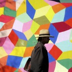 A man walks in front of a colorful mural along Market Street in San Francisco. <span class=
