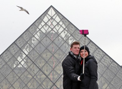 Chris Baker and Jennifer Hinson from Nashville, Tennessee, use a selfie stick in front of the Louvre Pyramide in Paris.
