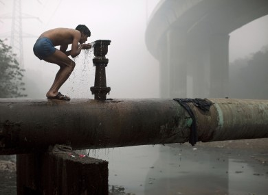 A man in New Delhi, India, drinks water from a tap near a sewage drain.