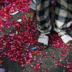 An Indian Sufi Muslim devotee, who arrived walking barefoot from New Delhi, stands on a road covered with rose petals thrown by locals during a procession as part of the Urs festival at the shrine of Sufi saint Khwaja Moinuddin Chishti in Ajmer, India.<span class=