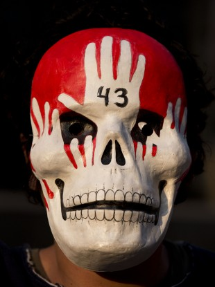 A protester wears a mask in memory of the 43 students found buried after bieng killed by a criminal gang.