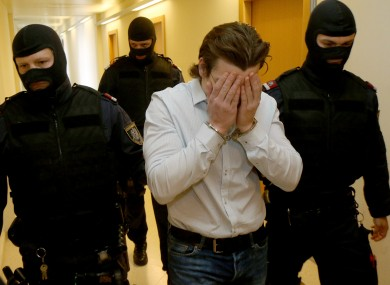A 19-year-old suspected Islamic State supporter, center, is surrounded by officers when arriving for his trial at the main court in Vienna, today.