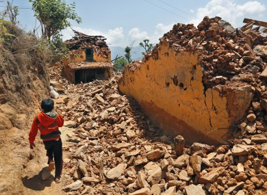 A Nepalese boy runs past houses destroyed in Pauwathok village, Sindhupalchok.