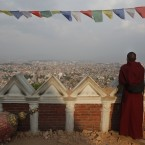 A Buddhist monk catches an aerial view of Kathmandu from the damaged Swayambhunath Stupa premises in Kathmandu, Nepal. The April 25 earthquake killed thousands and injured many more as it flattened mountain villages and destroyed buildings and archaeological sites in Kathmandu. <span class=