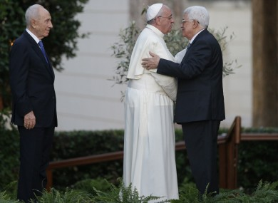 Pope Francis and Palestinian President Mahmoud Abbas embrace each other.