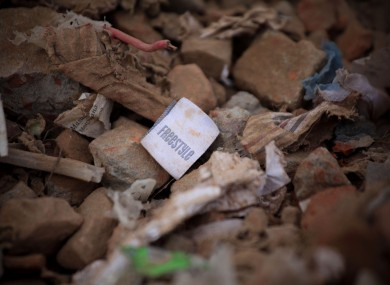 A clothes tag sits among the rubble of the Rana Plaza factory collapse.