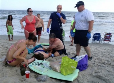 People help a teenage girl at the scene of a shark attack in North Carolina.