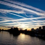 Globalized transportation networks, especially commercial aviation, are a major contributor of air pollution and greenhouse gas emissions, like the chem-trails seen here in the west London sky over the River Thames.<span class=