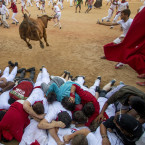 A cow jumps over revelers during a cow show in the bull ring, at the San Fermin Festival, in Pamplona, Spain, Tuesday, July 14, 2015. Revelers from around the world arrive in Pamplona every year to take part in the eight days of the running of the bulls.<span class=