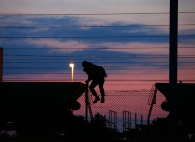 A migrant climbing the fence on to the tracks at the Eurotunnel site