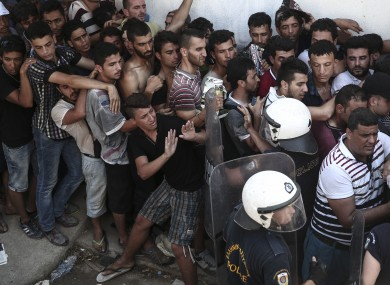 Police officers try to make space as migrants queuing for a registration procedure inside a stadium in Kos