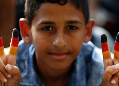 A young boy with the German flag painted on his fingers at a railway station in Budapest, Hungary