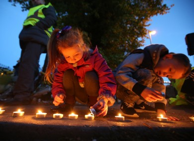 Children lay candles near the site on Glenamuck Road