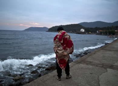 An Afghan refugee walks by the sea on the island of Lesbos, Greece, after arriving from Turkey yesterday