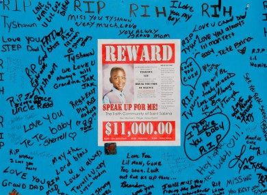 A reward sign and messages hang near where Tyshawn Lee was fatally shot in Chicago.