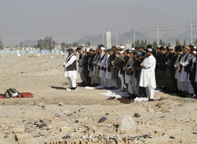 Afghan men pray for Mohammad Sami, a young man killed during clashes at the airport.
