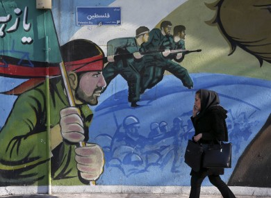 An Iranian woman walks past a mural depicting Iranian armed forces in the battlefield, at Palestine Square.