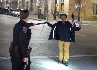 Police stop a boy as he walks away from a crowd that formed after the shooting.
