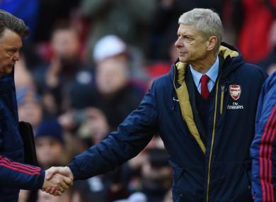 Louis van Gaal and Arsene Wenger shake hands.