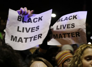 Protesters hold up signs during a demonstration against the deaths of two unarmed black men at the hands of white police officers in New York City and Ferguson.