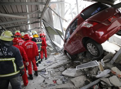 Rescue workers search a collapsed building from an early morning earthquake in Tainan, Taiwan.