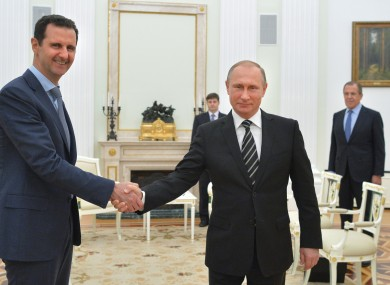 In this file photo taken on Tuesday, Oct. 20, 2015, Russian President Vladimir Putin, center, shakes hand with Syrian President Bashar Assad as Russian Foreign Minister Sergey Lavrov, right, looks on