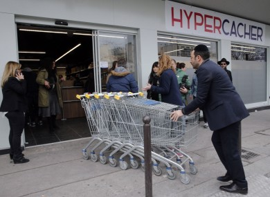 A worker pushes trolleys into the Hyper Cacher, the scene of a deadly attack in January 2015, during its reopening.