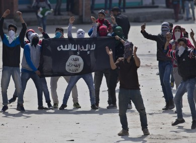 Kashmiri Muslims hold an Islamic State flag aloft.