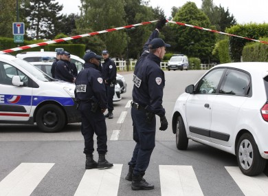 French police officers work at the crime scene the day after a knife-wielding attacker stabbed a senior police officer to death.