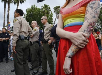 A woman stands next to Los Angeles County Sheriff's deputies and police as they gather prior to the Gay Pride parade in West Hollywood, California yesterday.
