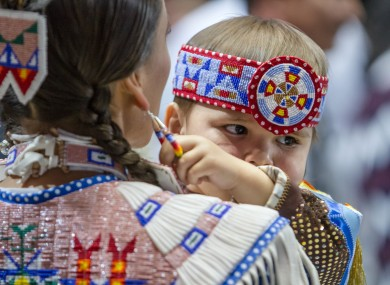 Omani Clairmont, age 2, pulls on his mother, Tanksi Clairmont's ear ring at the annual Gathering of Nations of North American native tribes.